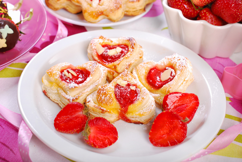 heart shaped puff pastry cookies with strawberries on white plate for valentines